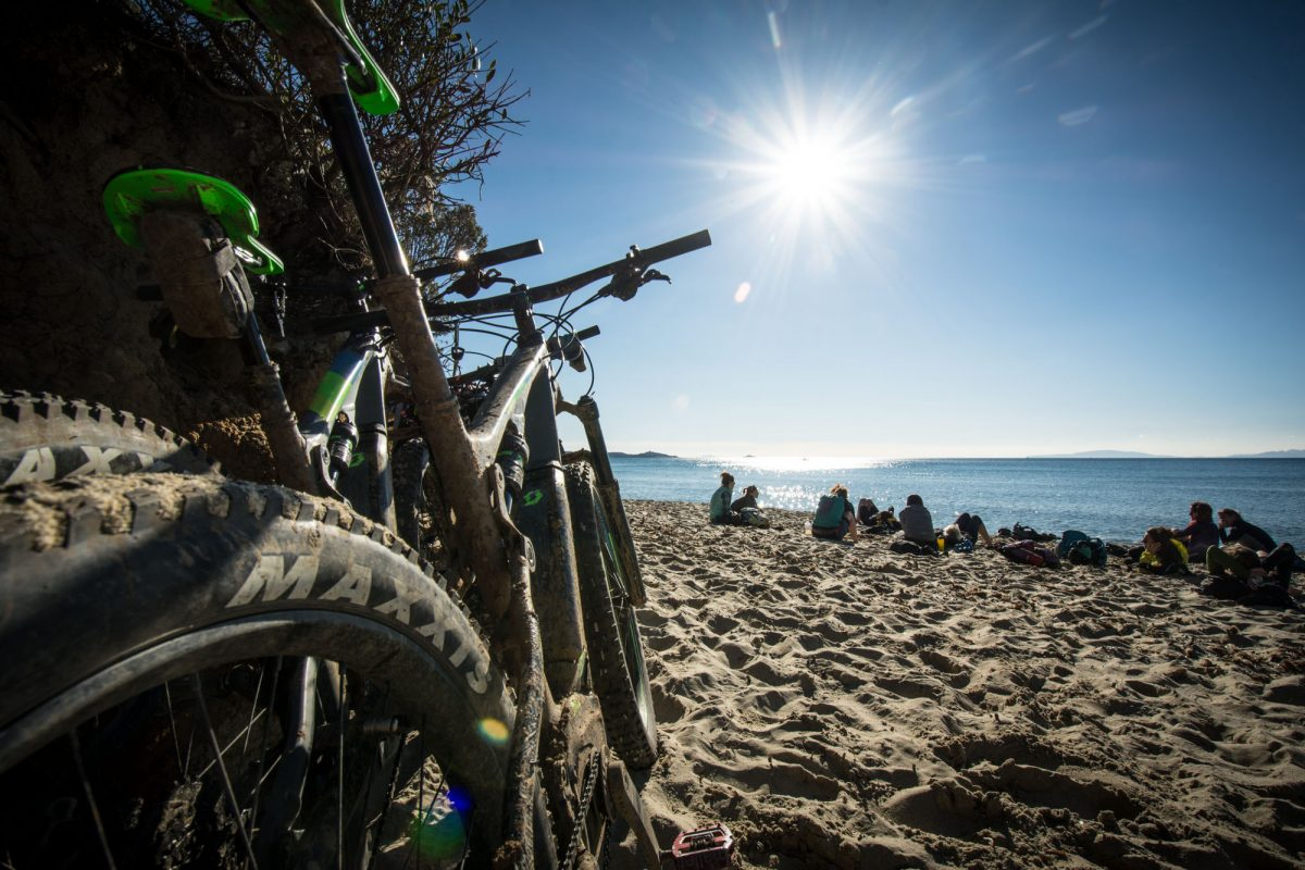 pedalare d'inverno in mountain bike donne in bici si riposano silla spiaggia di Calaviolina
