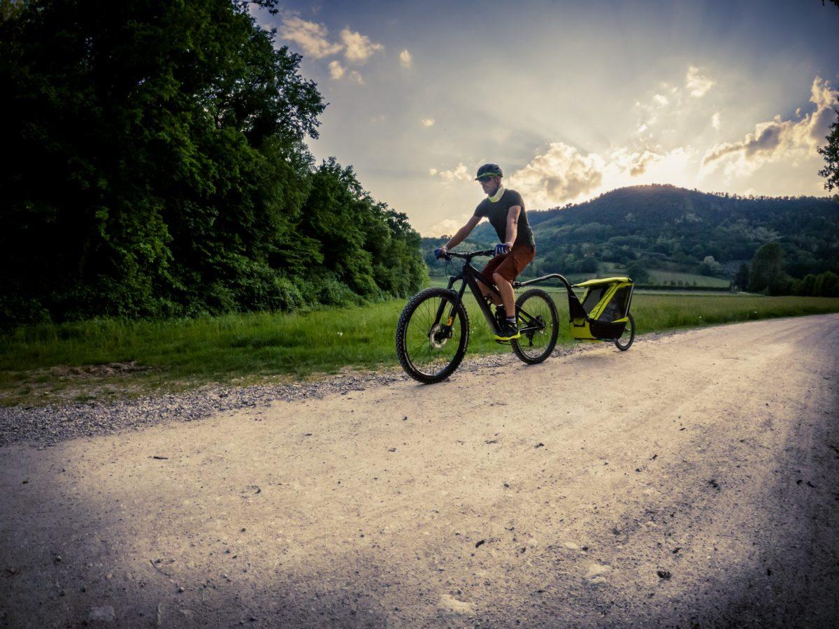 carrello bici con bimbo in ciclabile sterrata con papà in mountain bike
