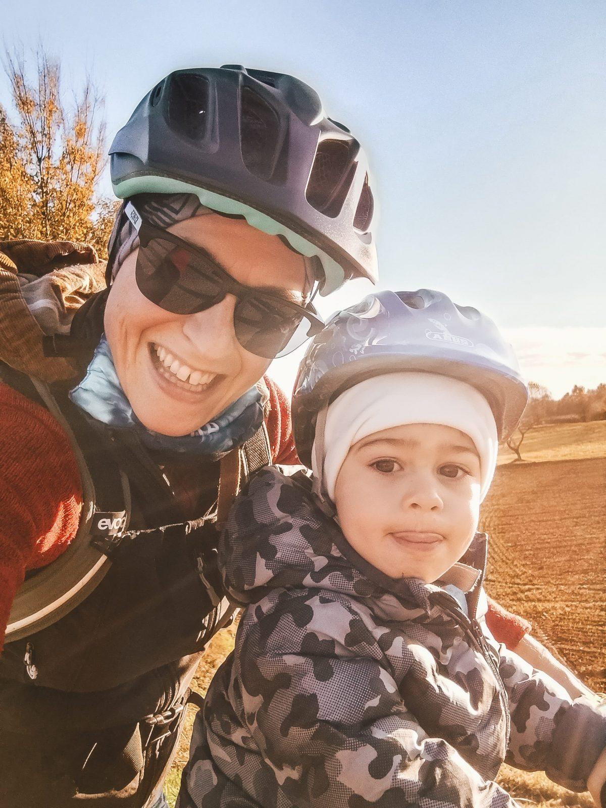 Bambino con casco in bici con la mamma