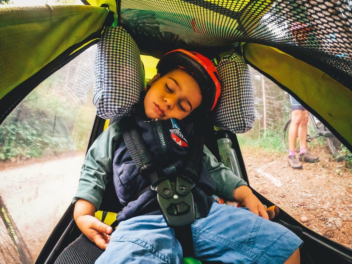 Bambino dorme nel carrellino da bici
