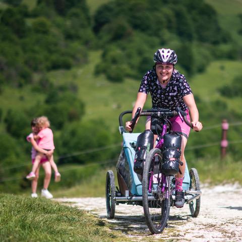 mamma in bicicletta con carrellino e figli