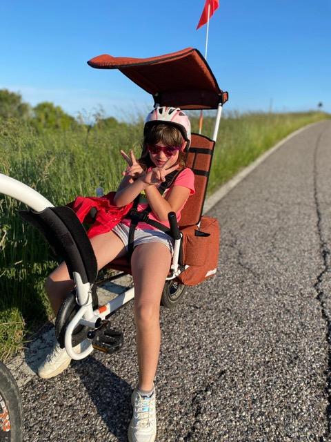 La piccola Nicola nel suo carrellino da bici